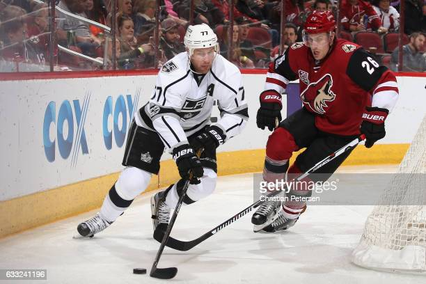 Jeff Carter of the Los Angeles Kings skates with the puck ahead of Michael Stone of the Arizona Coyotes during the third period of the NHL game at...