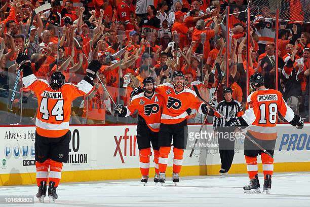 Jeff Carter of the Philadelphia Flyers celebrates with teammates Kimmo Timonen Simon Gagne and Mike Richards after scoring an emptynet goal in the...