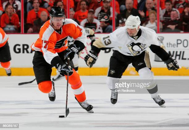 Jeff Carter of the Philadelphia Flyers skates the puck across center ice against Bill Guerin of the Pittsburgh Penguins during Game Three of the...