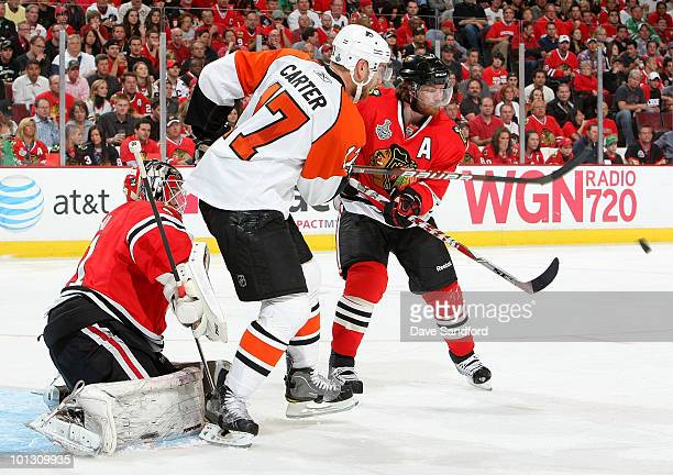 Jeff Carter of the Philadelphia Flyers watches as a 32 foot slapshot from Simon Gagne gets past goaltender Antti Niemi and Duncan Keith of the...