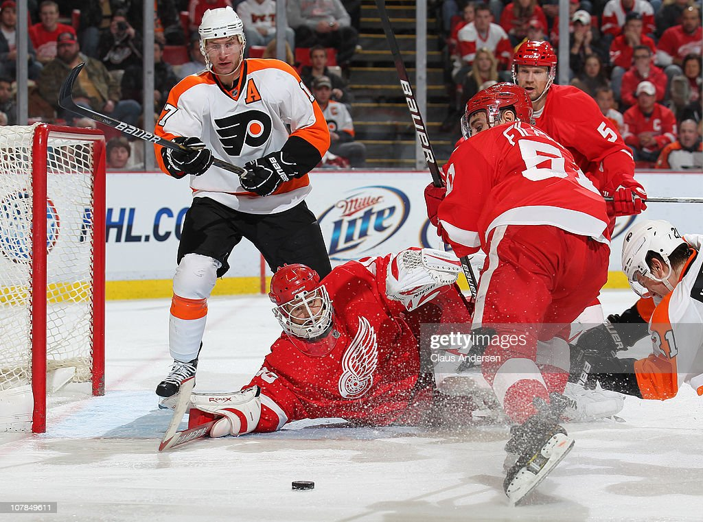 Jeff Carter #17 of the Philadelphia Flyers watches as Chris Osgood #30 of the Detroit Red Wings makes a sprawling save in a game on January 2, 2011 at the Joe Louis Arena in Detroit, Michigan. The Flyers defeated the Wings 3-2.