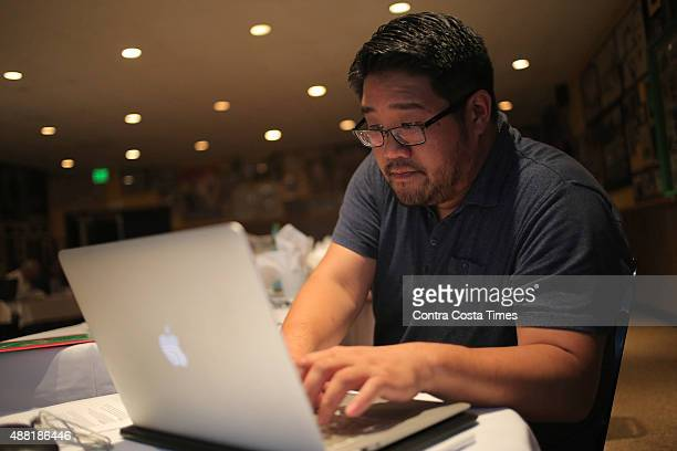 Jeff Chung a member of the Greater Oakland Professional Pigskin Prognosticators League enters information into a laptop during the group's annual...