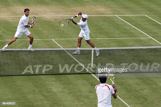 Jeff Coetzee of South Africa plays a backhand playing with Jordan Kerr of Australia during the men's doubles semi final match against Marcelo Melo of...
