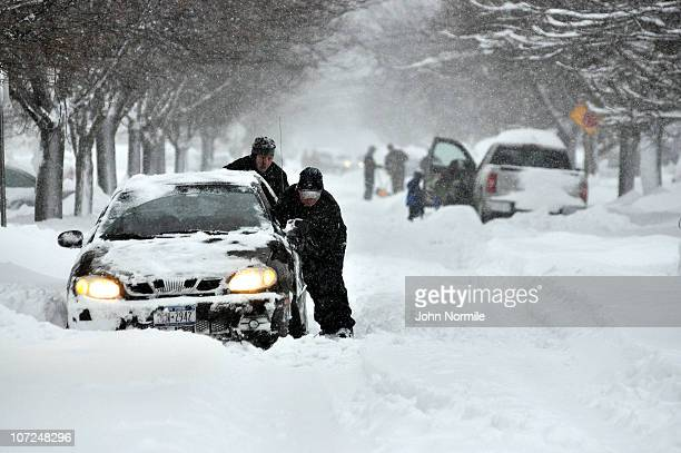Jeff Conrad and Matt Kearns attempt to help a stranded motorist after a five mile wide band of lake-effect snow dumped more than two feet of snow and...