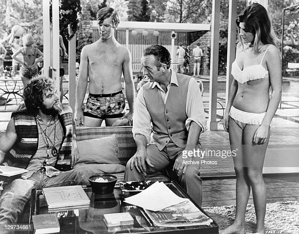 Jeff Cooper and Mike McGeevey get talked to by David Niven while Cristina Ferrare looks on in a scene from the film 'The Impossible Years' 1968