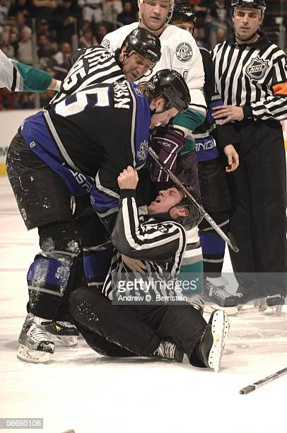 Jeff Cowan of the Los Angeles Kings helps linesman Pat Dapuzzo up off the ice after he tried to separate Cowan and Todd Fedoruk of the Anaheim Mighty...