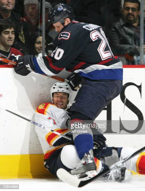 Jeff Cowan of the Vancouver Canucks checks Steve Montador of the Florida Panthers into the ice during their NHL game January 7, 2007 at General...