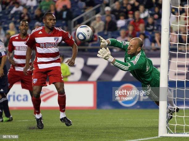 Jeff Cunningham of FC Dallas presses goalie Preston Burpo of the New England Revolution who makes a save late in the second half at Gillette Stadium...