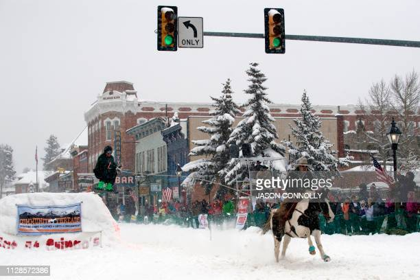 Jeff Dahl races down Harrison Avenue while skier Greg Dahl airs out off the first jump of the Leadville ski joring course during the 71st annual...