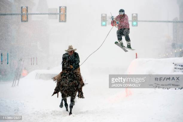 Jeff Dahl races down Harrison Avenue while skier Jason Dahl airs out off the final jump of the Leadville ski joring course during the 71st annual...
