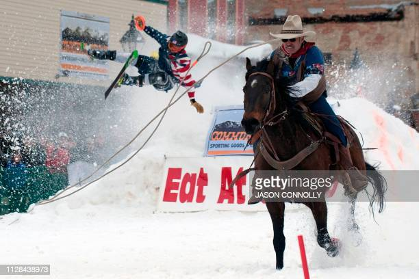 Jeff Dahl races down Harrison Avenue while skier Vincent Pestello looses control of the first jump of the Leadville ski joring course during the 71st...