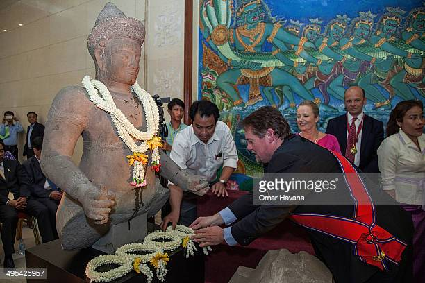Jeff Daigle Deputy Chief of Mission of the Embassy of the United States of America deposits a traditional Cambodian crown of flowers in front of the...