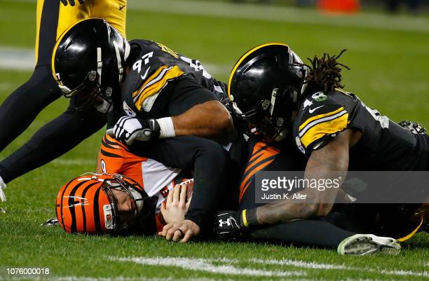 Jeff Driskel of the Cincinnati Bengals is sacked by Bud Dupree of the Pittsburgh Steelers and Cameron Heyward in the third quarter during the game at...