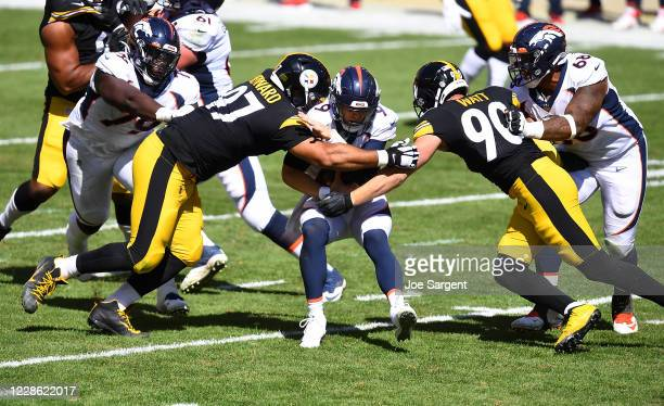Jeff Driskel of the Denver Broncos is sacked by Cameron Heyward and T.J. Watt of the Pittsburgh Steelers during the second quarter at Heinz Field on...
