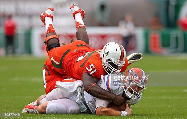 Jeff Driskel of the Florida Gators is tackled by Shayon Green of the Miami Hurricanes during a game at Sun Life Stadium on September 7 2013 in Miami...