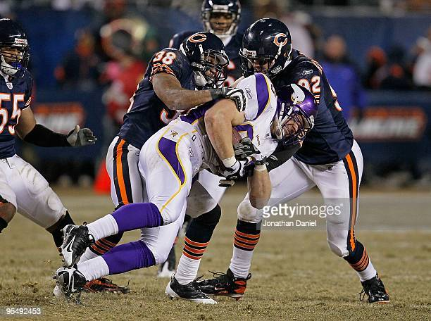 Jeff Dugan of the Minnesota Vikings is brought down by Danieal Manning and Hunter Hillenmeyer of the Chicago Bears as teammate Lance Briggs moves in...