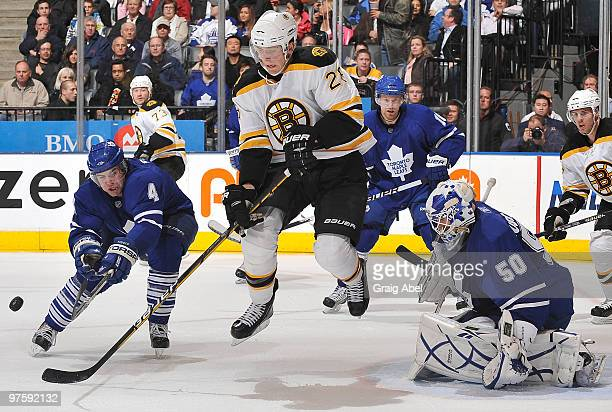 Jeff Finger of the Toronto Maple Leafs battles for the puck with Blake Wheeler of the Boston Bruins in front of goalie Jonas Gustavsson during game...