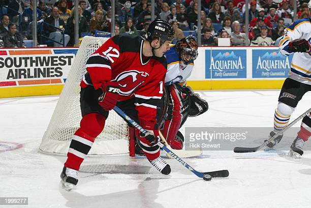 Jeff Friesen of the New Jersey Devils readies to make a backhand shot on goaltender Mika Noronen of the Buffalo Sabres during the NHL game at HSBC...