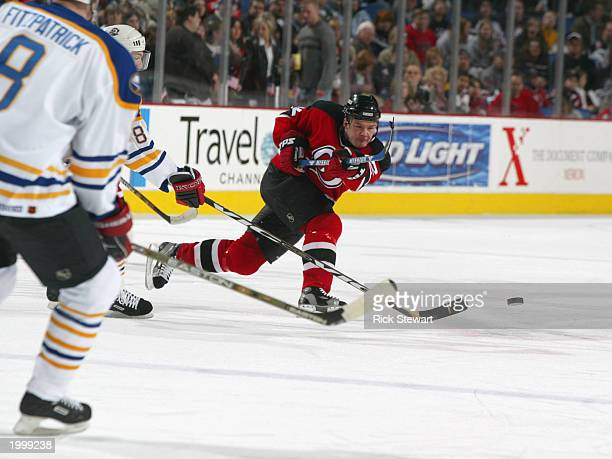 Jeff Friesen of the New Jersey Devils slaps the puck from center ice deep into the Buffalo Sabres zone during the NHL game at HSBC Arena on April 6...