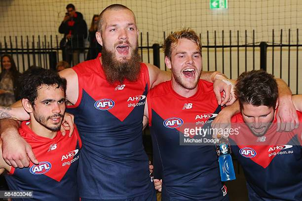 Jeff Garlett Max Gawn Jack Watts and Jesse Hogan of the Demons celebrate the win with fans during the round 19 AFL match between the Melbourne Demons...