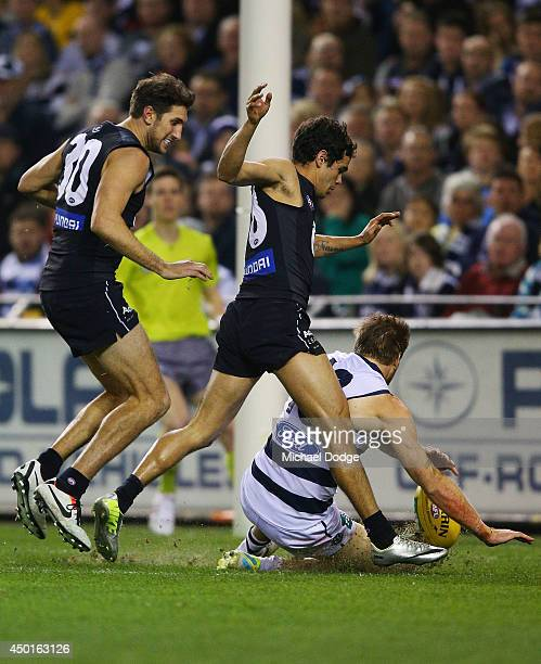 Jeff Garlett of the Blues kicks the ball for goal past Tom Lonergan of the Cats that was given as a point by the goal umpire during the round 12 AFL...