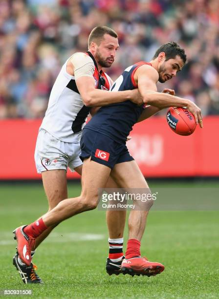 Jeff Garlett of the Demons kicks whilst being tackled by Jarryn Geary of the Saints during the round 21 AFL match between the Melbourne Demons and...