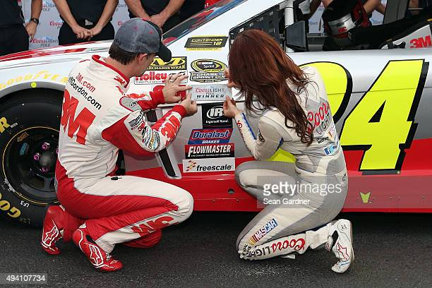 Jeff Gordon driver of the 3M Chevrolet and Miss Coors Light Amanda Merts place the Pole Winner's decal on his car after qualifying for the pole...