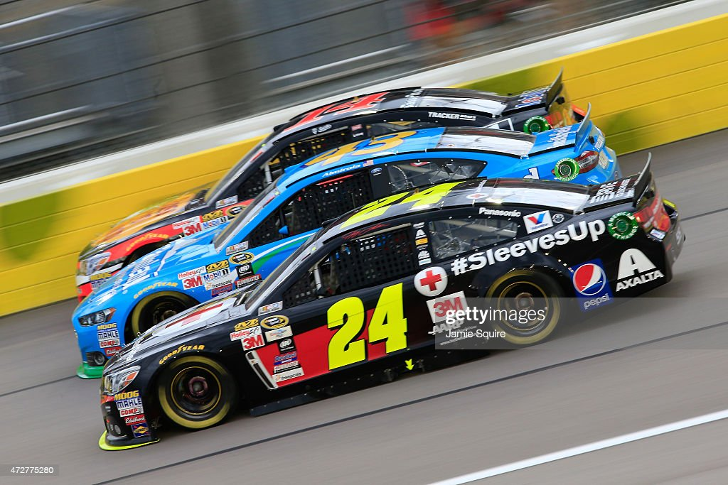 Jeff Gordon, driver of the #24 American Red Cross Chevrolet, Aric Almirola, driver of the #43 Farmland Ford, and Tony Stewart, driver of the #14 Bass Pro Shops/Mobil 1 Chevrolet, race during the NASCAR Sprint Cup Series SpongeBob SquarePants 400 at Kansas Speedway on May 9, 2015 in Kansas City, Kansas.