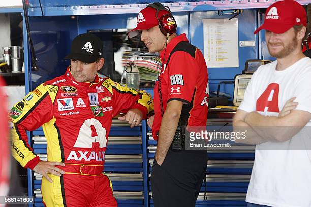 Jeff Gordon driver of the Axalta Chevrolet and crew chief Greg Ives talk in the garage as teammate Dale Earnhardt Jr looks on during practice for the...