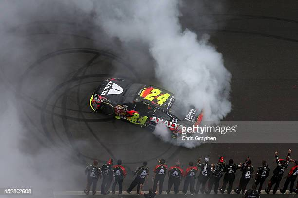 Jeff Gordon driver of the Axalta Chevrolet celebrates with a burnout after winning the NASCAR Sprint Cup Series Crown Royal Presents The John Wayne...
