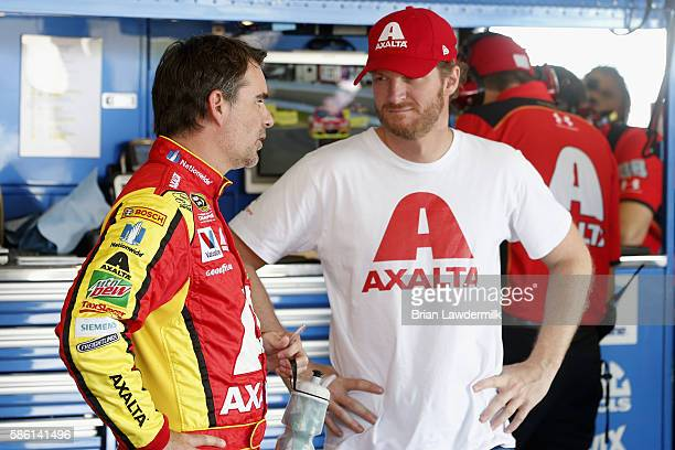 Jeff Gordon driver of the Axalta Chevrolet talks with teammate Dale Earnhardt Jr in the garage during practice for the NASCAR Sprint Cup Series...