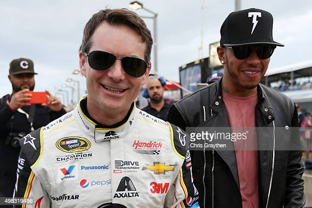 Jeff Gordon driver of the AXALTA Chevrolet walks with Formula One World Champion Lewis Hamilton during prerace ceremonies for the NASCAR Sprint Cup...