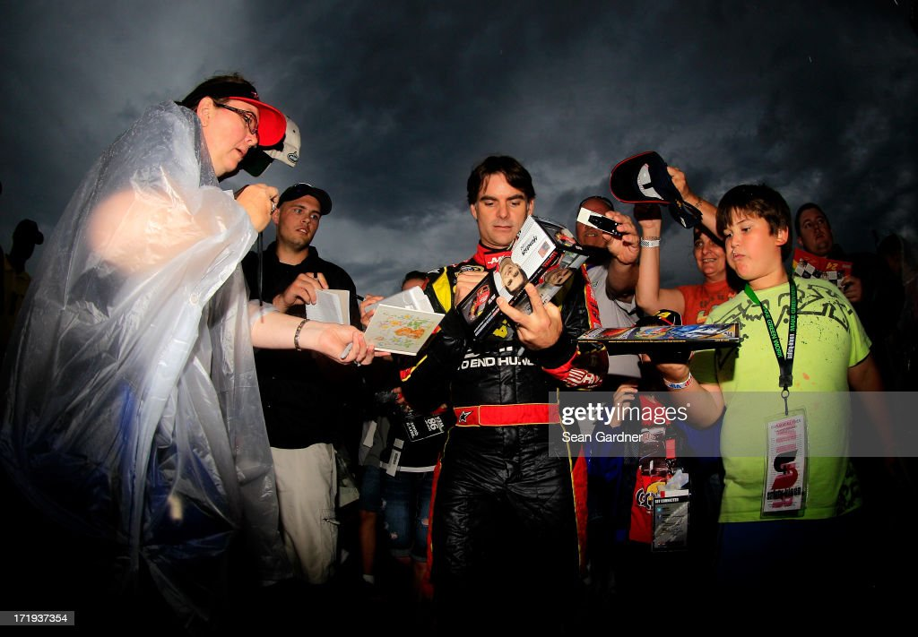 Jeff Gordon, driver of the #24 Drive to End Hunger Chevrolet, signs autographs as he walks to pre-race ceremonies for the NASCAR Sprint Cup Series Quaker State 400 at Kentucky Speedway on June 29, 2013 in Sparta, Kentucky.
