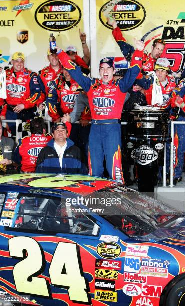 Jeff Gordon , driver of the Dupont Chevrolet, gestures as he and others celebrate his victory during the NASCAR Nextel Cup Daytona 500 on February...