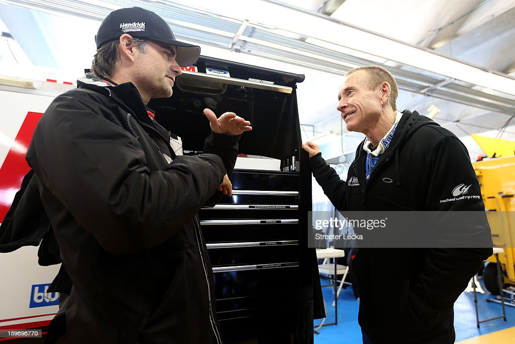Jeff Gordon, driver of the #24 Hendrick Motorsports Chevrolet, talks to Mark Martin, driver of the #55 Michael Waltrip Racing Toyota, in the garage area during NASCAR Testing at Charlotte Motor Speedway on January 18, 2013 in Charlotte, North Carolina.