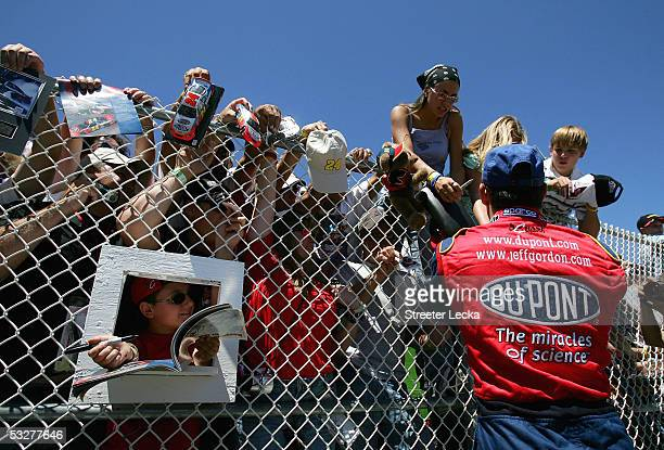 Jeff Gordon, driver of the Hendrick Motorsports DuPont Chevrolet, signs autographs during the NASCAR Nextel Cup Pennsylvania 500 qualifying on July...