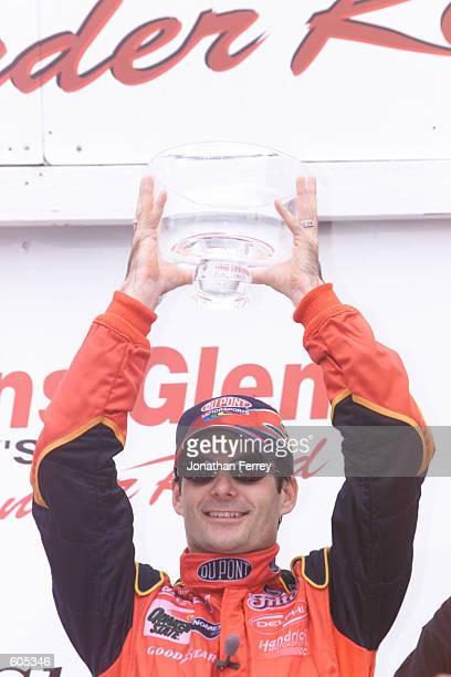 Jeff Gordon hoists the trophy after winning the NASCAR Winston Cup Series Global Crossing at the Glen at Watkins Glen International in Watkins Glen,...