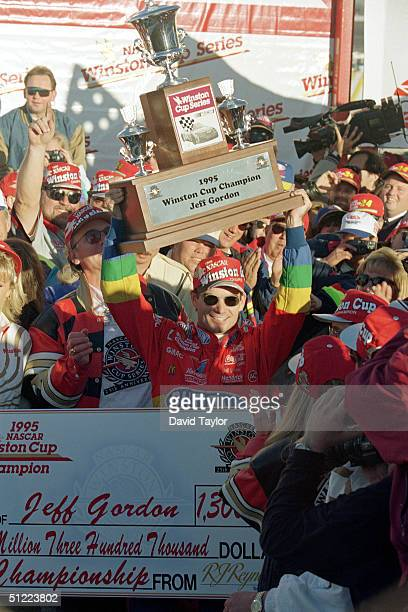 Jeff Gordon of DuPont Chevrolet hoist the Winston Cup championship trophy as he celebrates winning the NASCAR NAPA 500 at the Atlantic Motor Speedway...