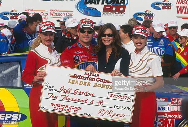 Jeff Gordon stands with two Winston Cup Girls and his wife Brooke to hold up a leader bonus award after racing his Dupont car during the Daytona 500...