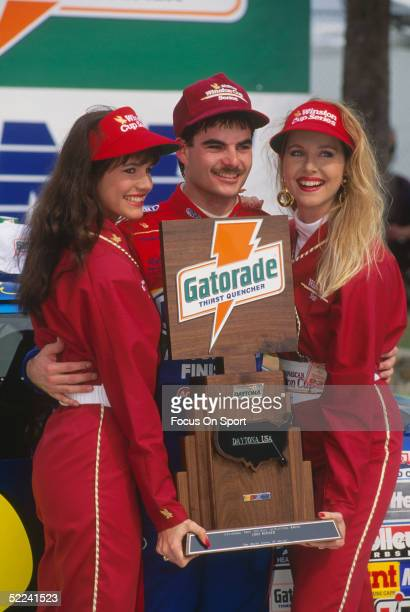 Jeff Gordon stands with two Winston Cup Girls and holds the 5th place award after racing his Dupont car during the Daytona 500 at the Daytona...