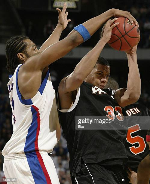 Jeff Graves of the Kansas Jayhawks stops Guillaume Yango of the Pacific Tigers during the second round game of the NCAA Division I Men's Basketball...