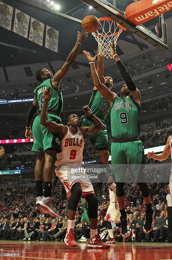 Jeff Green #8, Leandro Barbosa #12 and Rajon Rondo #9 of the Boston Celtics leap for a rebound over Loul Deng #9 of the Chicago Bulls at the United Center on December 18, 2012 in Chicago, Illinois. The Bulls defeated the Celtics 100-89.