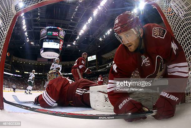 Jeff Halpern of the Phoenix Coyotes falls over goaltender Mike Smith into the net during the second period of the NHL game against the Minnesota Wild...