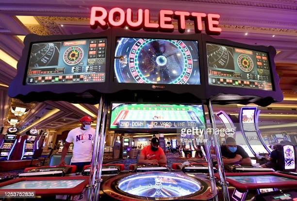 Jeff Hamilton Kwasi Tripp and Albert Robinson all of Tennessee play at a sociallydistanced electronic table game for roulette at Mandalay Bay Resort...