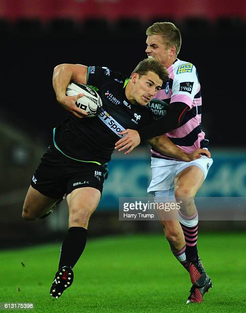 Jeff Hassler of Ospreys is tackled by Gareth Anscombe of Cardiff Blues during the Guiness Pro12 match between the Ospreys and Cardiff Blues at the...