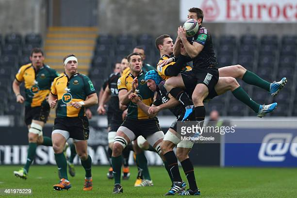 Jeff Hassler of Ospreys rises above George North of Northampton Saints to claim a high ball during the Heineken Cup Pool One match between Ospreys...