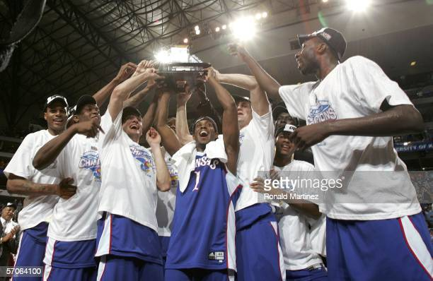 Jeff Hawkins of the Kansas Jayhawks hoists the championship trophy with the help of teammates after defeating the Texas Longhorns 8068 in the final...