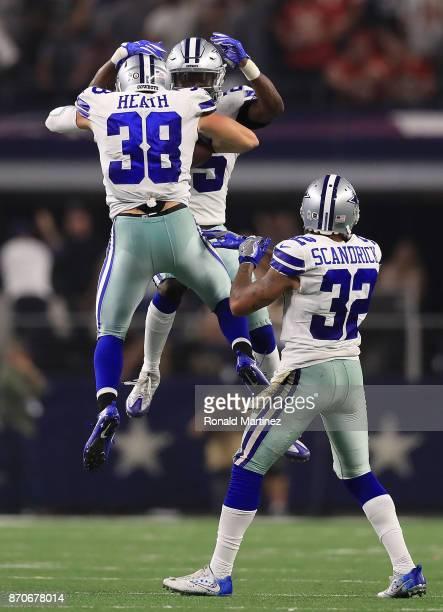 Jeff Heath of the Dallas Cowboys chest bumps Xavier Woods of the Dallas Cowboys as Orlando Scandrick of the Dallas Cowboys claps after Heath's...