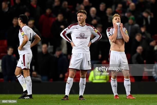 Jeff Hendrick Ben Mee and Jack Cork of Burnley look dejected on the final whistle during the Premier League match between Manchester United and...
