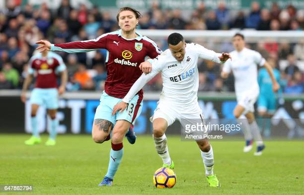 Jeff Hendrick of Burnley challenges Martin Olsson of Swansea City during the Premier League match between Swansea City and Burnley at The Liberty...